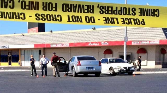 Crime scene tape is wrapped around a parking lot after a homicide at a nearby strip club on June 26, 2013. (Shannon Moore/FOX5)