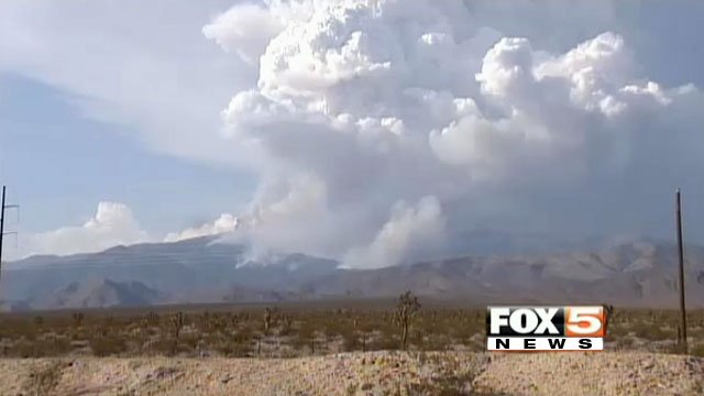 Smoke and flames rise from Mt. Charleston as the sun tries to shine through the haze on July 4, 2013. (FOX5)