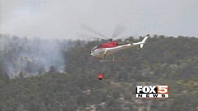 A helicopter swoops in over the Carpenter 1 wildfire on July 9, 2013, to dump water on the blaze. (FOX5)