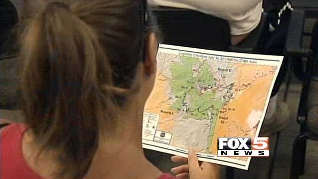 An evacuee looks over a map of the Carpenter 1 fire area during an information meeting on July 14, 2013. (FOX5)