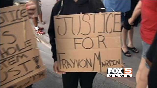 Protesters of the Zimmerman verdict carry signs through downtown Las Vegas on July 14, 2013. (FOX5)