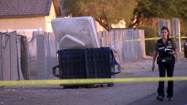 An investigator walks by a dumpster in Las Vegas where police say a body was found on Aug. 12, 2013. (FOX5)