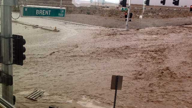 Flood waters race through the intersection of Brent Lane and Fort Apache Road on Aug. 25, 2013. (Source: FOX5 viewer Polly)