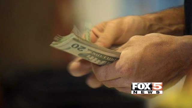 A person counts cash while waiting in line at a register in this undated imaged. (File/FOX5)