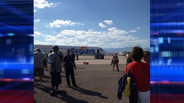 Passengers stand on the tarmac outside the evacuated plane. (Cheryl Dorsey)