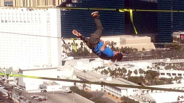 """A slackline walker holds on to the line during a so-called """"megastunt"""" at Mandalay Bay on Oct. 16, 2013. (Jason Valle/FOX5)"""