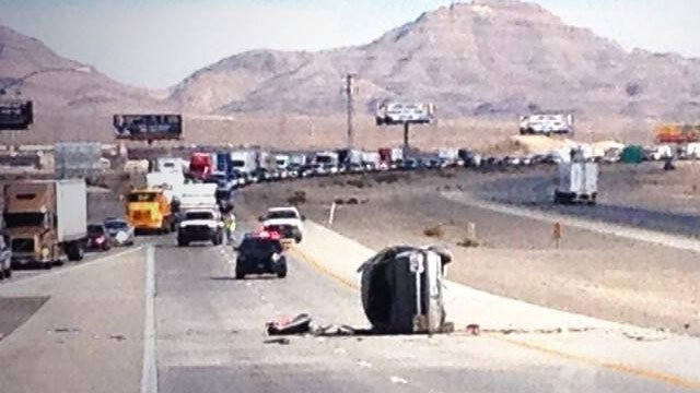 A vehicle laid on its side after a crash on Interstate 15 near Lamb Boulevard. NHP said the vehicle was traveling northbound but ended up on the southbound lanes.  (Christian Cazares/FOX5)