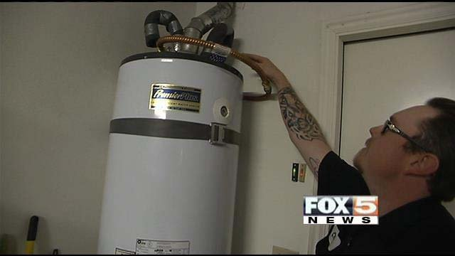 Chris Nartell with Silver State Refrigeration and HVAC inspects a water heater ahead of this week's projected freezing temperatures. (FOX5)