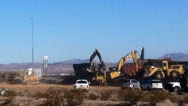 Heavy equipment scoops up coal Dec. 9, 2013, spilled after a train derailment near the Las Vegas Motor Speedway. (FOX5)