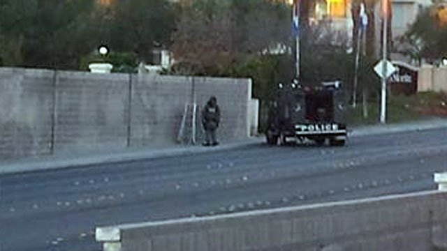 A man dressed in SWAT gear stands next to a police vehicle parked on Washington Avenue in western Las Vegas on Dec. 12, 2013. (Source: FOX5 ReportIt user geannap)