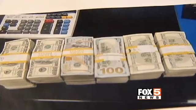 Stacks of cash found inside a Las Vegas taxi are displayed on a table. (FOX5)