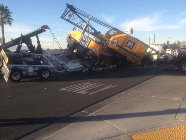 A crane sits partially off the truck that was hauling it along Rainbow Road near Lake Mead Boulevard on Monday, Dec. 30. (Jason Valle/FOX5)
