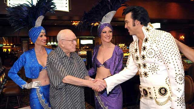 Hotel and gaming pioneer Jackie Gaughan is greeted by an Elvis impersonator and showgirls as he celebrates his 89th birthday at the El Cortez Hotel and Casino in downtown Las Vegas on Oct. 24, 2009. (AP/Las Vegas News Bureau/Glenn Pinkerton)