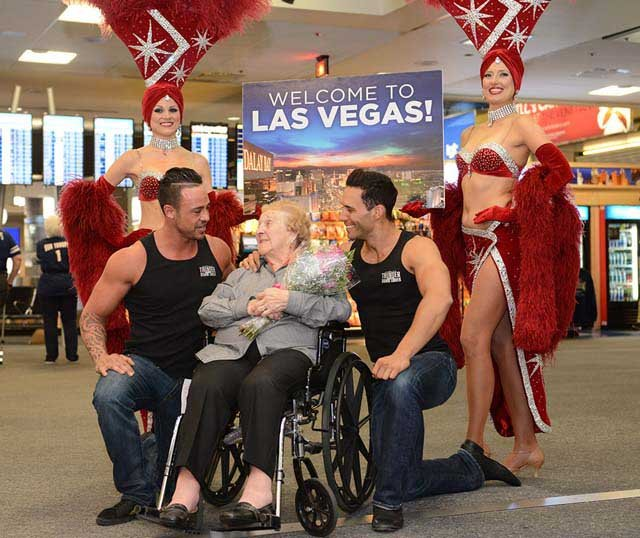 Evelyn Kottman, 103, is greeted at McCarran Airport by showgirls and dancers from Thunder From Down Under on Friday, April 18. (Source: Las Vegas News Bureau/Darrin Bush)