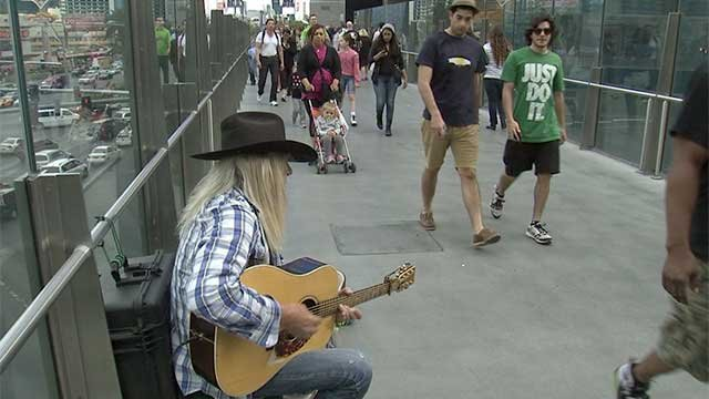 Marv, a street musician in Las Vegas, strums his guitar as tourists pass. (FOX5)