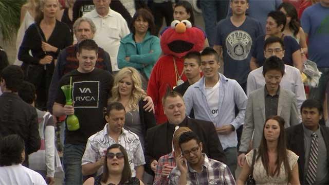 A person dressed as Elmo walks along the Las Vegas Strip with tourists. (FOX5)