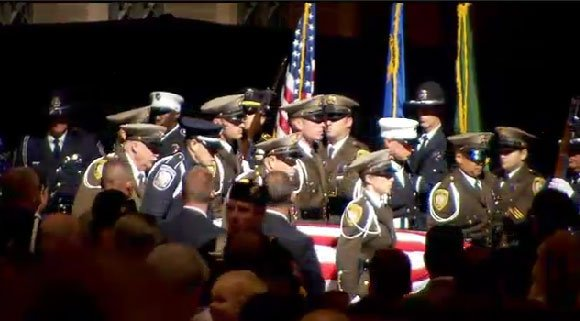 Pallbearers carry the casket of Officer Alyn Beck inside Smith Center for services on June 14, 2014. (FOX5)