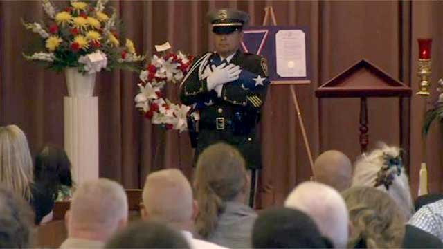 A member of the Las Vegas Metro Police Honor Guard prepares to present a folded American flag to the Wilcox family. (Justin Grant/FOX5)