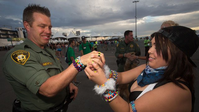 A Las Vegas Metro police K9 handler interacts with an attendee of the Electric Daisy Carnival during the 2014 event's second night on June 21, 2014. (Source: Curious Josh for Insomniac Productions)