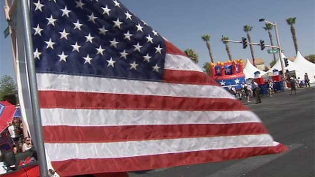 An American flag waves as the Summerlin Patriotic Parade marches past in the background July 4, 2014. (Peter Dawson/FOX5)
