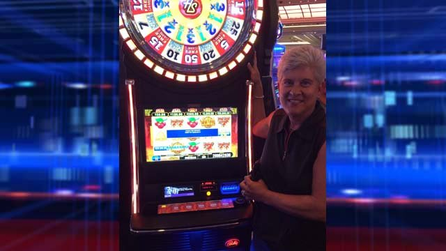 Susan Cupit poses next to the video slot machine that paid out more than $2.6 million. (Source: The Firm Public Relations & Marketing)