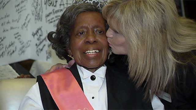 Dorothy Brooks, better known as Ms. Dorothy, is kissed on the cheek by a co-worker during her 90th birthday party July 23, 2014. (FOX5)