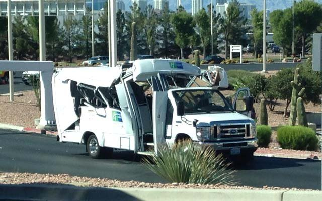A damaged hotel shuttle bus sits at the entrance of the Terminal 1 passenger pickup area at McCarran Airport on Thursday, July 24. (Source: Matt Finn)