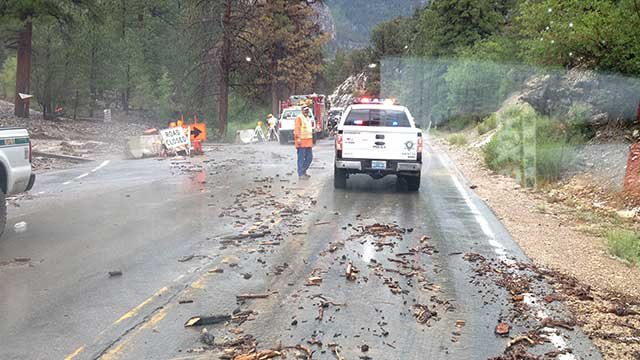 Crews block part of a road in Rainbow Canyon as they work to clear it of debris July 28, 2014. (Les Krifaton/FOX5)