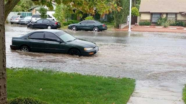 A car navigates a flooded road in southwest Las Vegas on Aug. 4, 2014. (FOX5 Report It)