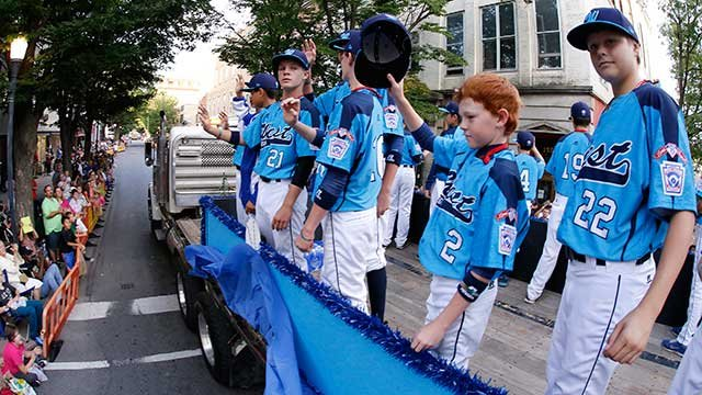 In this photo taken with a fisheye lens members of the Mountain Ridge Little League team from Las Vegas, NV., ride in the Little League Grand Slam Parade as it makes its way through downtown Williamsport, Pa., Wednesday, Aug. 13, 2014. (AP Photo/Gene J.