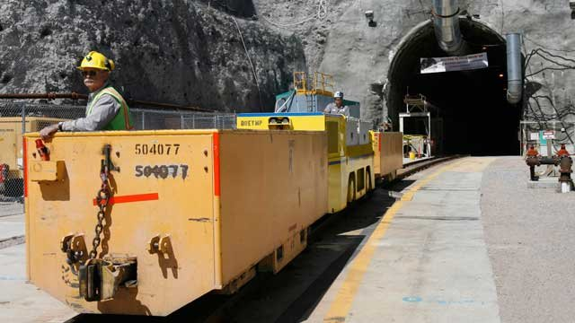 FILE - In this April 13, 2006 file photo, Pete Vavricka conducts an underground train from the entrance of Yucca Mountain in Nevada. (AP Photo/Isaac Brekken, File)