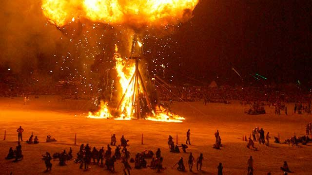 "Burning Man participants watch a 40-foot wooden figure know as ""The Man"" burn on the playa at the Black Rock Desert near Gerlach, Nev., on Saturday, Sept. 1, 2007, during the Burning Man festival. (AP Photo/Brad Horn)"