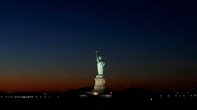 Light from the setting sun gives a backdrop to the Statue of Liberty, Tuesday, Sept. 23, 2014, in New York. (AP Photo/Julio Cortez)