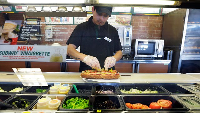 In this March 3, 2015 photo, Roberto Castelan makes a sandwich at a Subway sandwich franchise in Seattle. (AP Photo/Ted S. Warren)