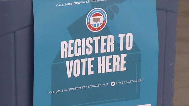 A sign at a booth shows unregistered voters where they can register. (File/FOX5)
