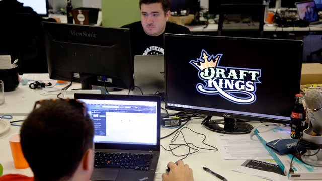 FILE- In this Sept. 9, 2015, file photo, Len Don Diego, marketing manager for content at DraftKings, a daily fantasy sports company, works at his station at the company's offices in Boston. (AP Photo/Stephan Savoia, File)
