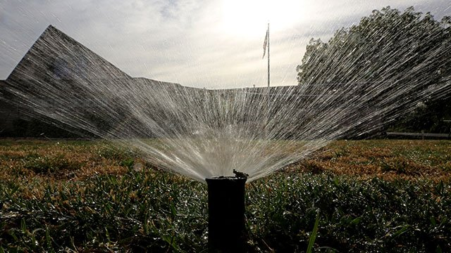 FILE - In this July 15, 2014, file photo, sprinklers water a lawn in Sacramento, Calif. Most Californians have heard by now that they should stop watering their lawns to save water in the drought. (AP Photo/Rich Pedroncelli, File)