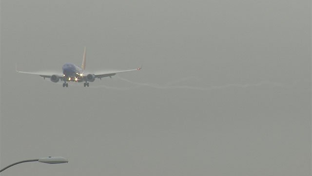 An airplane appears from the low clouds as it lands at McCarran International Airport on Jan. 5, 2016.